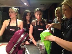Young women watching baking master class macaron batter ready for piping