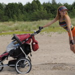 a packed sporty stroller and a young mom on the beach