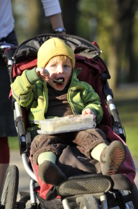 a boy in a jogging stroller having meal from his launch box