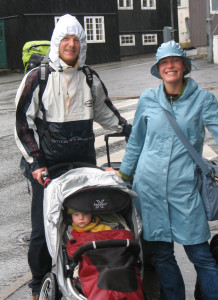 Two parents with a stroller wearing rin proof jackets