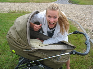 A mom posing with a baby stroller