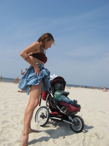 a mom on the beach with a jogging stroller