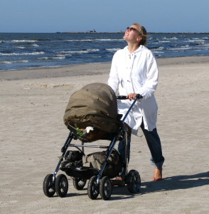 mom walking on the beach with the baby pram
